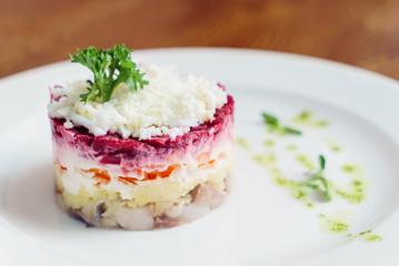 layered salad with herring, beets, carrots, onions, potatoes and eggs close-up on a plate