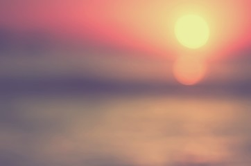 Blur tropical sunset beach with bokeh sun light wave abstract background.