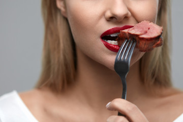 Woman Eating Food. Closeup Of Girl's Face Biting Meat Steak