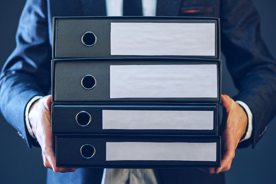Businessman with corporate files in four document binder