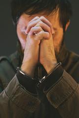 Handcuffed male prisoner in military uniform is praying