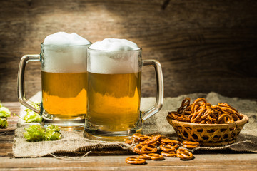 Couple glasses of beer froth with hop and pretzels