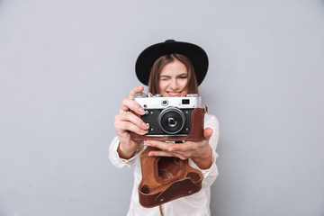 Woman in hat holding retro camera and taking photo