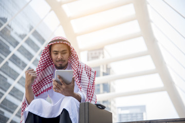 Handsome Arab Man Using Tablet computer while sitting in the city. Business success concepts.