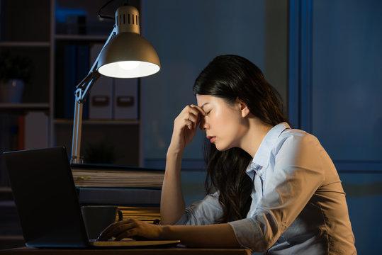 asian business woman headache overtime working late night