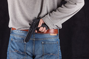 hand with a gun behind his back