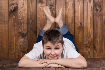 Teenager lying on his stomach. Against the background of the wooden planks