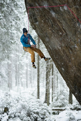 Rock climber on a challenging ascent. Extreme climbing. Unique winter sports. Scandinavian nature.