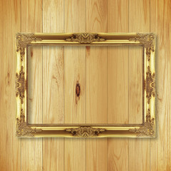 Antique gold frame on wooden wall ;. Empty picture frame on whit