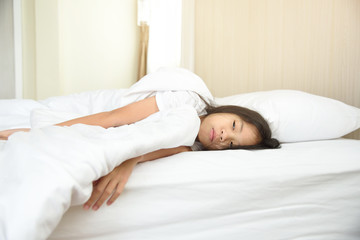 Do not want to wake up or illness concept. Portrait of lazy and touchy young Asian preteen age girl  in bed waking up late. Unhappy sleepy kid get up late in the morning.