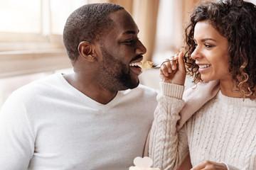 Joyful African American couple enjoying the cupcake in the cafe