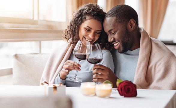 Joyful African American couple drinking wine in the restaurant