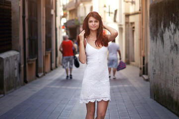Young woman tourist walking on the street in white dress, summer fashion style, travel to Europe