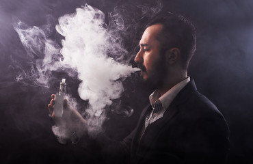Man using an advanced personal vaporizer or e-cigarette, close up; low-key image.