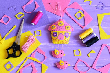 Decorative felt house with birds. Sewing materials and tools on wooden background. Homemade felt wall decoration to create beautiful and original interior design. Handicraft concept. Top view