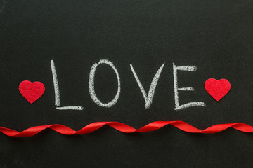 Love text written on chalkboard with a red ribbon