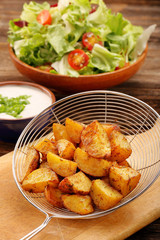 Fresh baked potatoes with salad and white dip