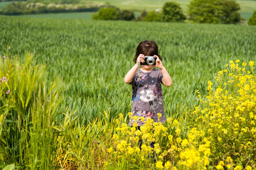 Little Girl taking a picture and enjoying photography in the beautiful rural landscapes of Warwickshire, England.