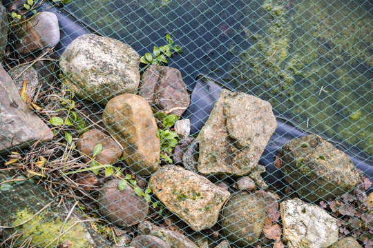 Netting covering a garden pond held in place by natural rocks and stones over a black plastic liner in a landscaping concept
