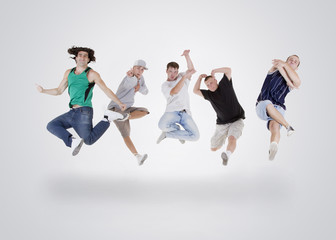 Group of young teenagers jumping over white