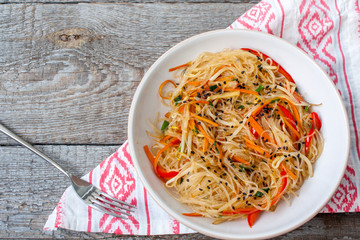 Rice noodles with vegetable stir fry on the ceramic bowl on dark wooden background