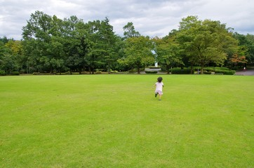 芝生の公園を走る少女