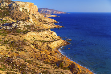 Beautiful seascape. Red beach on the island of Crete. A mountain range stretches along the Libyan Sea.