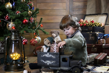 small child playing with toys with christmas decorations