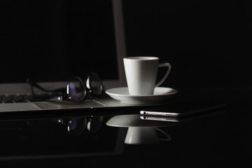 cup of coffee and smart phone over dark background