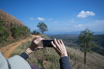 Women taking photo with smart phone at mountain peaks on holiday