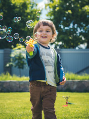 Cheerful sunny child starts soap bubbles from a toy gun. The emotion of happiness, fun, joy of kid. Smile of a toddler and sunny day.