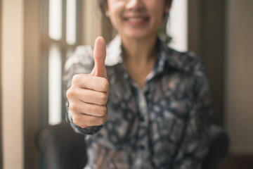 Woman showing thumbs up. Portrait of a young woman showing thumbs up.