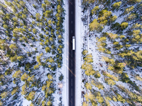 Aerial photo of lorry truck on the road surrounded by winter forest