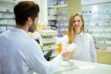Experienced pharmacist counseling female customer in modern phar