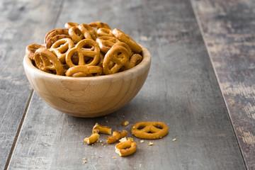 Salted pretzels in bowl on wooden background