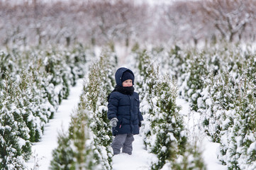 Baby boy in warm snowsuit walking in the winter park with a white snow.