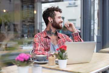 Young tattooed hipster using his laptop, sat outside a cafe