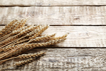 Ears of wheat on a grey wooden table