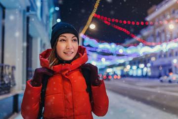 woman walking on the street at Christmas garland illumination de