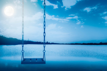 Empty swing set with sea and sky at  full moon night background,feel sad or lonely concept