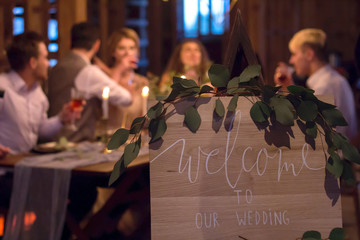 Wedding feast. Guests sit at festively decorated table.