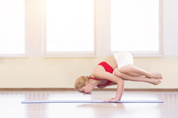 Young woman in white doing yoga pose arm balance