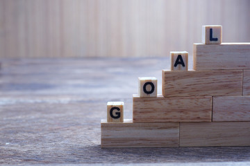 """A horizontal photographic image of a series of wood blocks structures in steps topped with the word """" GOAL """" in order to demonstrate the process towards achievement."""