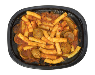 Rigatoni pasta with meatballs and sausage TV dinner top view isolated on a white background.