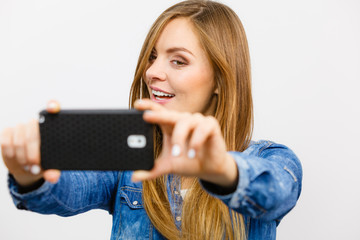 Woman in denim shirt taking self picture with phone