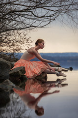 Ballerina in ballet pose sits above the lake on background of sk