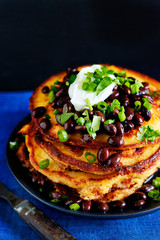Stack of savoury pancakes with beans, high angle view