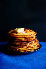 Stack of golden pancakes with melting butter