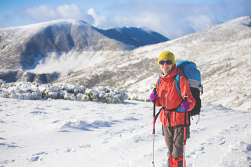 Girl with backpack walking on snow in the mountains.