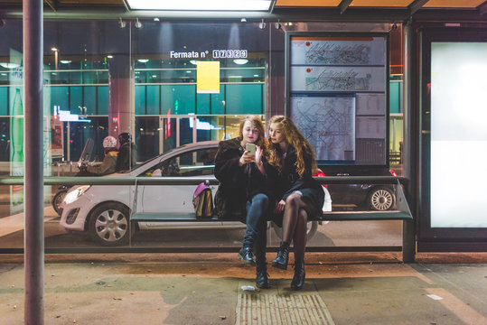 Two young beautiful caucasian women friends outdoor in the city night using smart phone hand hold sitting at bus stop - technology, social network communication concept